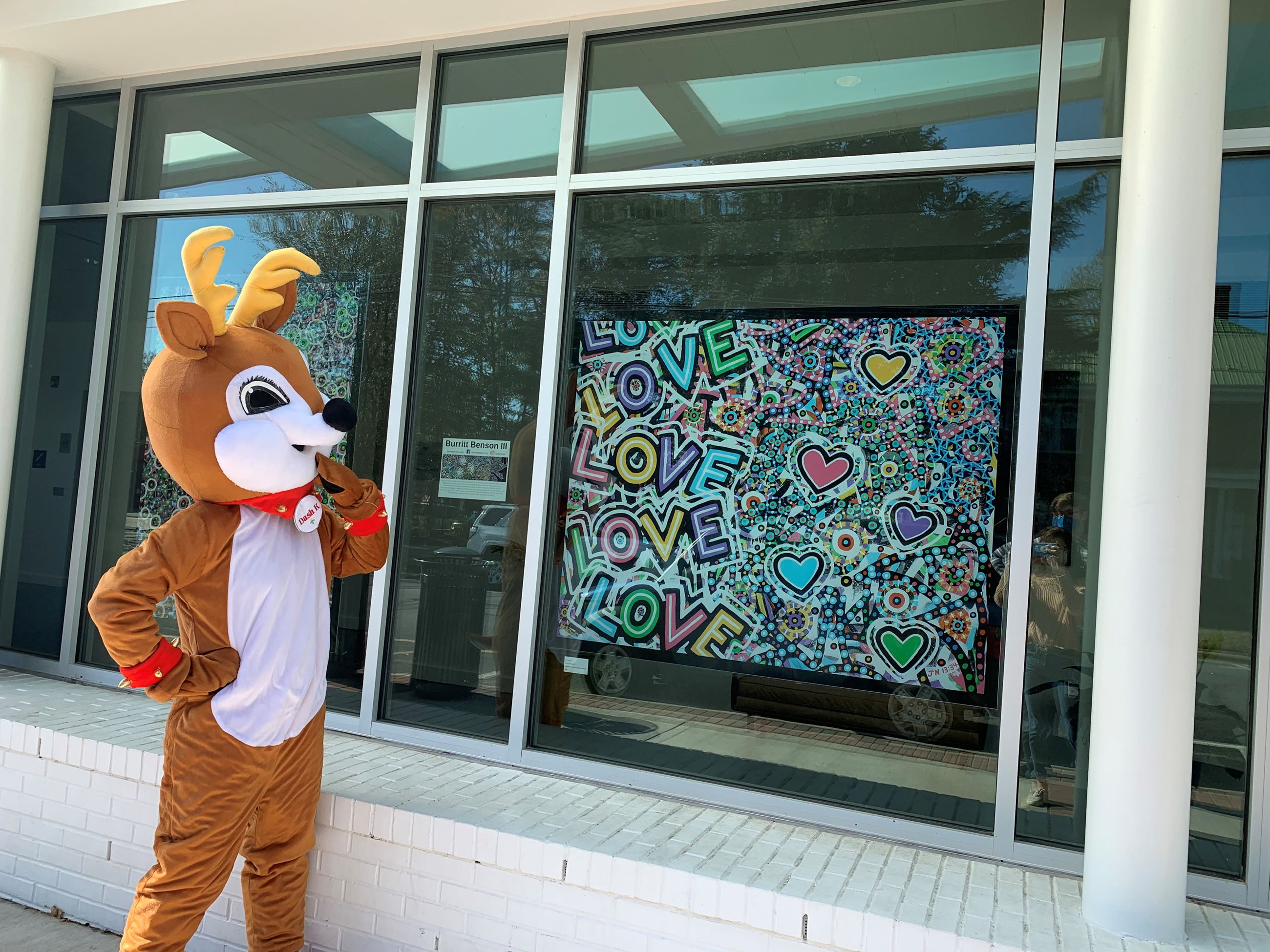 Dasher the reindeer standing outside the arts center looking at a painting