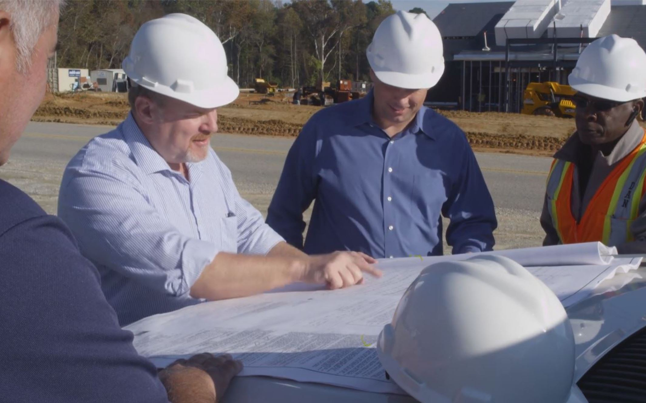Town Engineers Looking At Engineering Plans on a Construction Site
